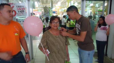 Clientes durante su visita a supermercado recibían cintas rosadas y globos junto a un brochure informativo.