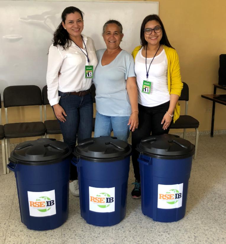 Colaboradores de Grupo IB haciendo entrega de basureros a la Directora Onelia Castellanos, del centro educativo.
